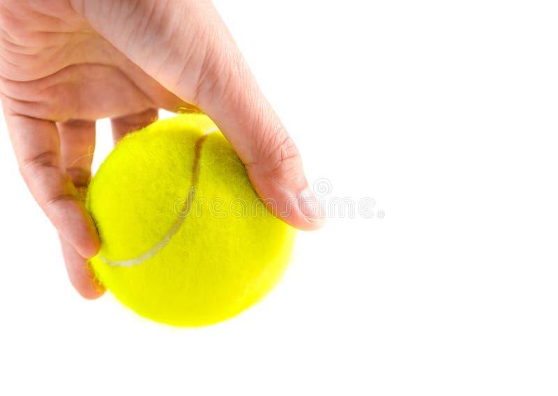 拿着在白色背景,准备服务位置的左手新的黄色网球 免版税库存照片