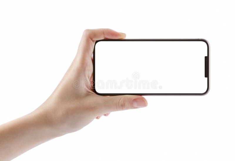 拿着在白色裁减路线的女孩手黑智能手机 免版税库存图片