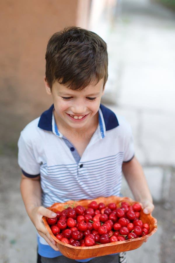 拿着在碗的愉快的矮小的兴高采烈的孩子樱桃 库存照片