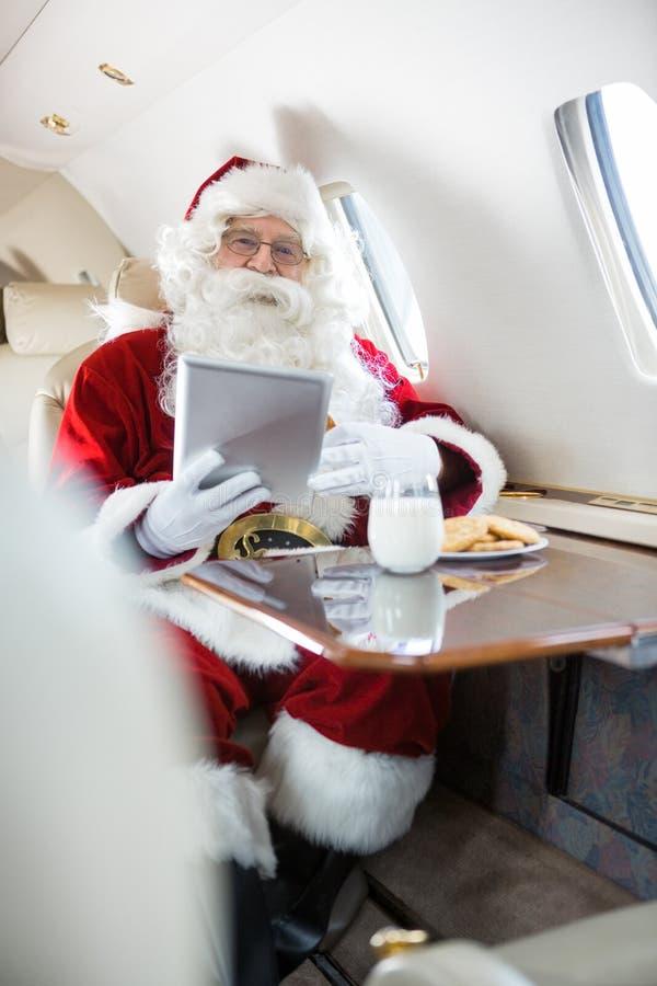 拿着在私人喷气式飞机的圣诞老人数字式片剂 图库摄影