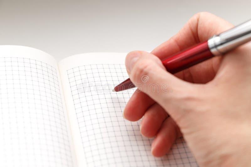 拿着在空的笔记本的女性手一支红色圆珠笔 库存图片