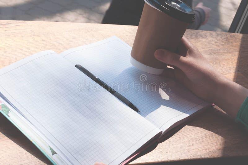 拿着在笔的有拷贝空间的Wooman纸杯和笔记本在木桌上在咖啡馆 免版税图库摄影