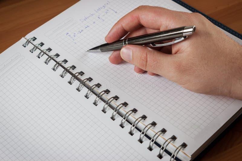 拿着在笔记本的一支灰色笔和学习算术的人 免版税库存图片