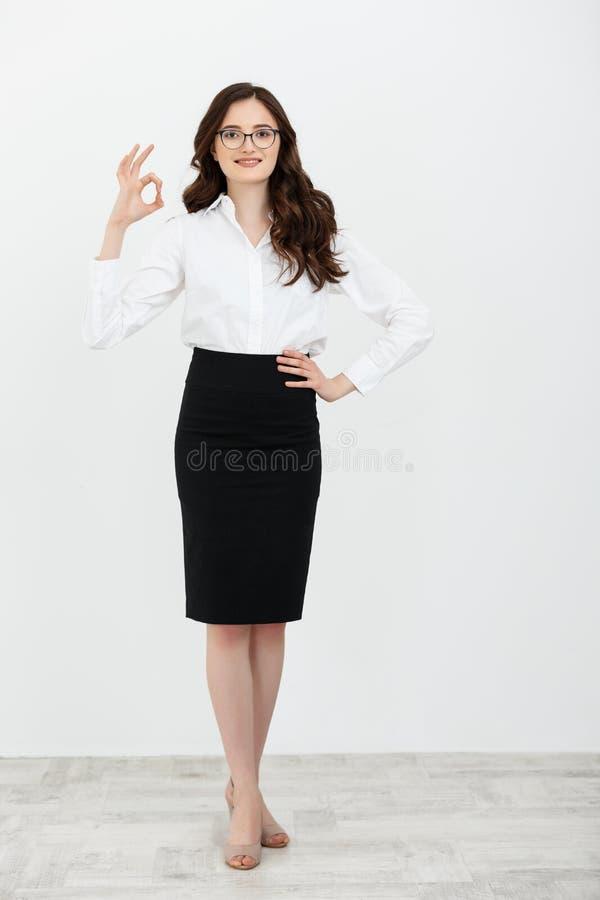 拿着在简单的白色背景的女商人画象好手指标志在演播室 免版税库存照片