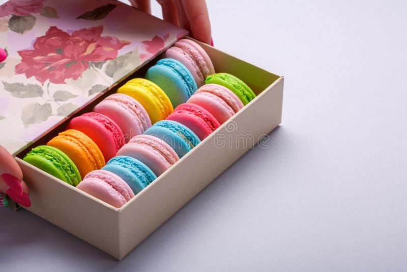 拿着在箱子的女孩五颜六色的法国蛋白杏仁饼干在手上 免版税库存照片