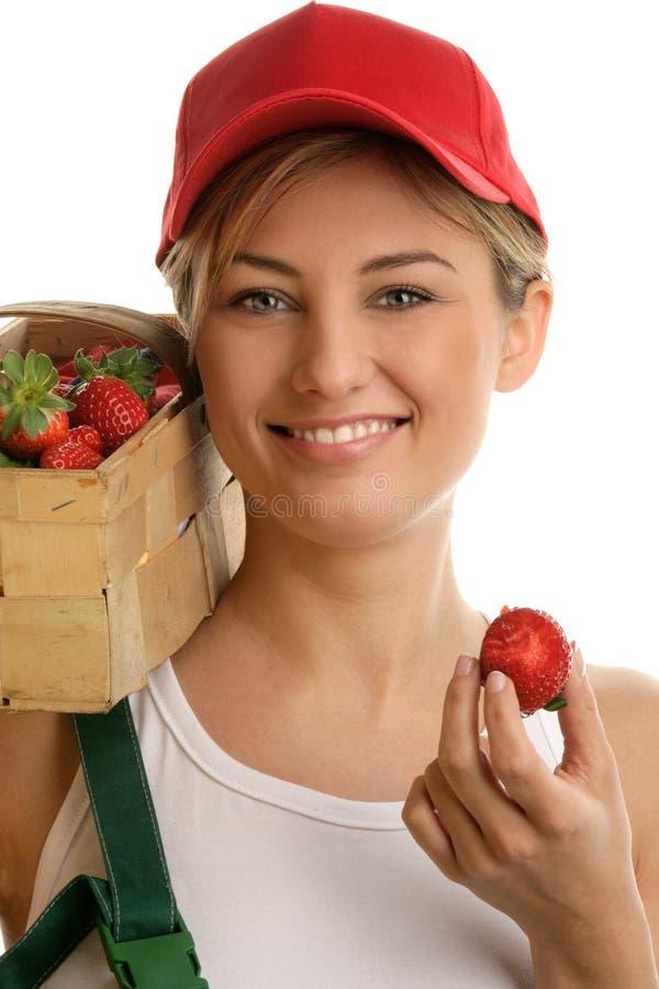 拿着在篮子的少妇新鲜的草莓 免版税库存图片