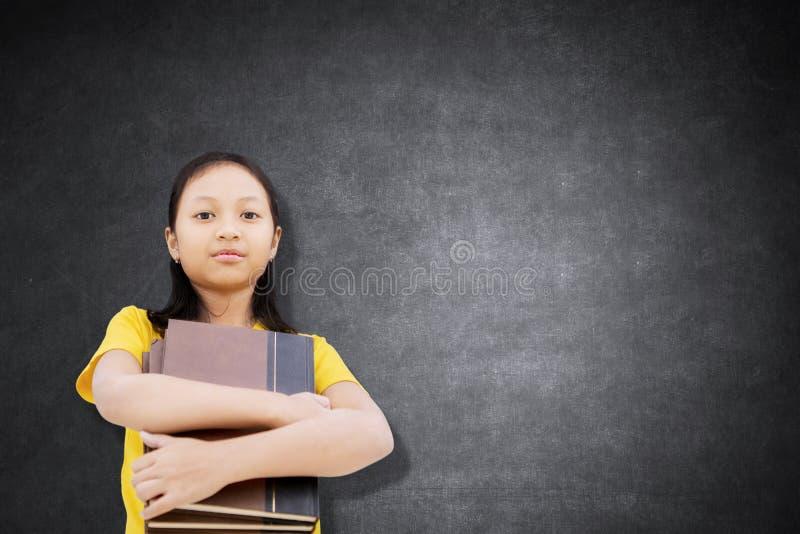 拿着在类的确信的女生书 免版税库存图片
