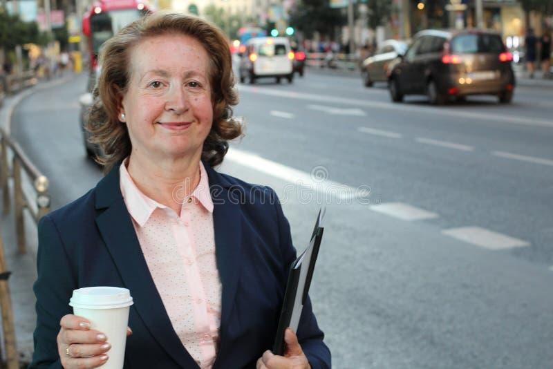 拿着在繁忙的城市街道的白肤金发的微笑的女实业家一次性杯子有拷贝空间的 图库摄影