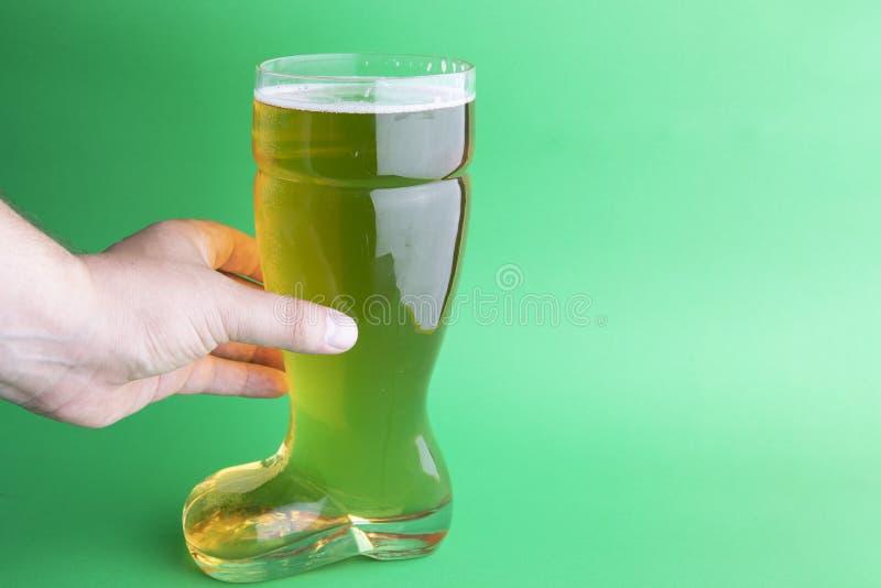 拿着在绿色背景的啤酒起动的人手 库存图片