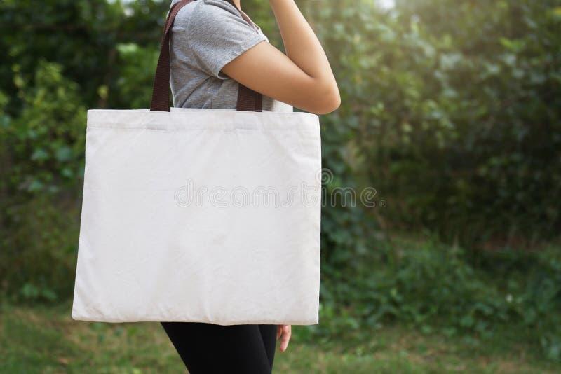 拿着在绿色背景的妇女手棉花袋子 Eco 免版税库存图片