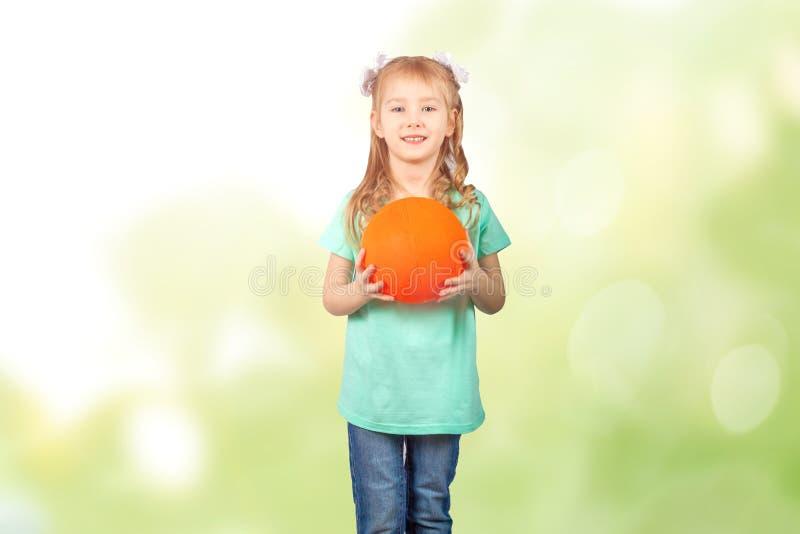 拿着在美好的bokeh背景的小女孩一个球 免版税库存照片