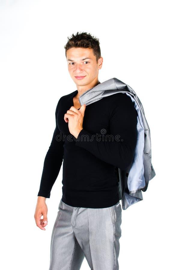 拿着在肩膀的年轻人外套查出在空白backgrou 库存图片