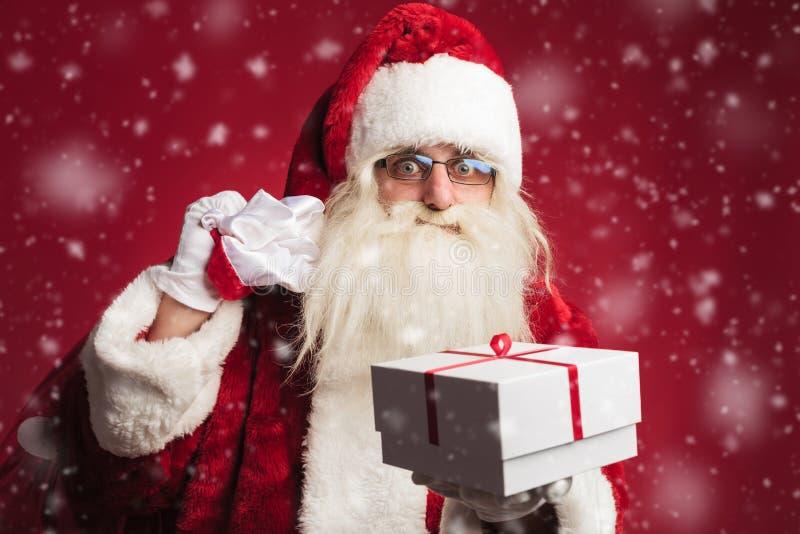 拿着在肩膀的袋子和提供礼物的圣诞老人 免版税库存照片