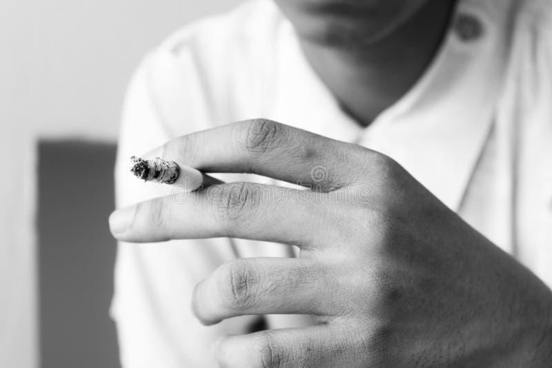 拿着在背景的手灼烧的香烟 免版税库存图片