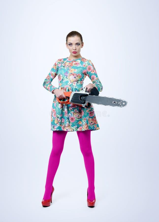拿着在背景的礼服的女孩电锯 有工具概念的妇女 免版税库存照片