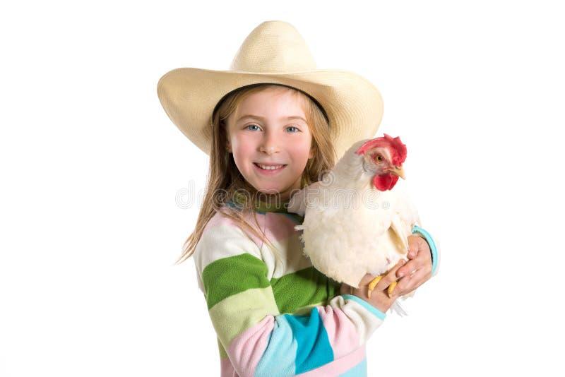 拿着在胳膊的白肤金发的孩子女孩农夫白色母鸡 免版税库存照片