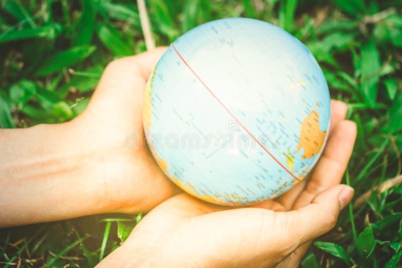 拿着在自然绿色背景的女性手浮动地球 免版税库存照片