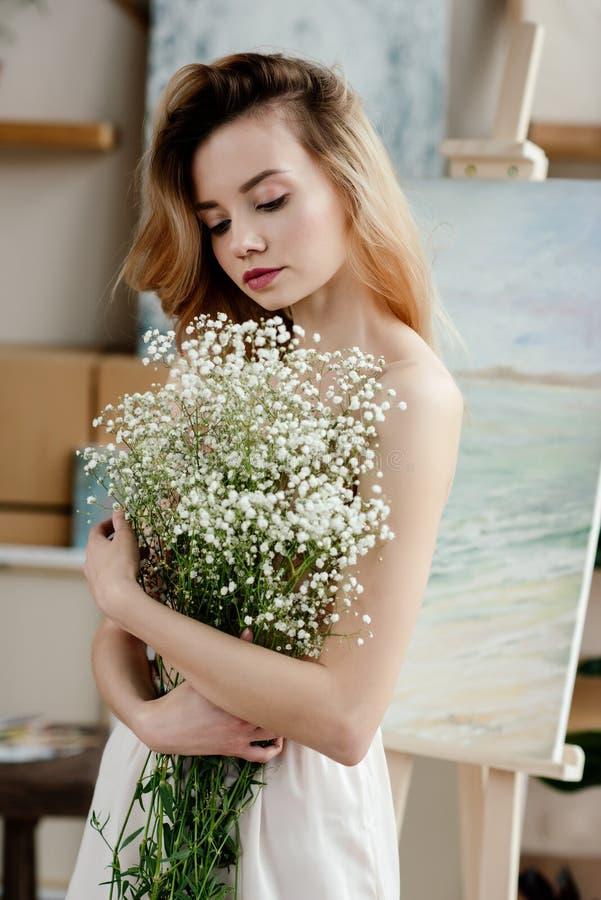 拿着在艺术的美丽的嫩女孩白花 库存图片