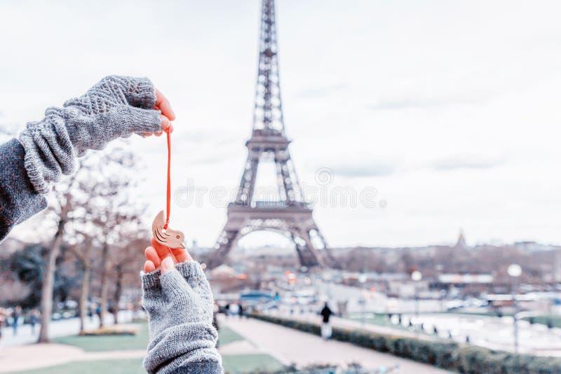 拿着在艾菲尔铁塔背景的妇女小的陶瓷鸟 法国巴黎 免版税库存照片