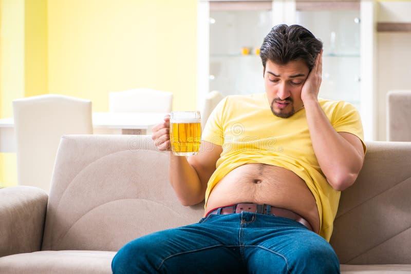 拿着在节食的概念的肥胖肥胖人啤酒 图库摄影