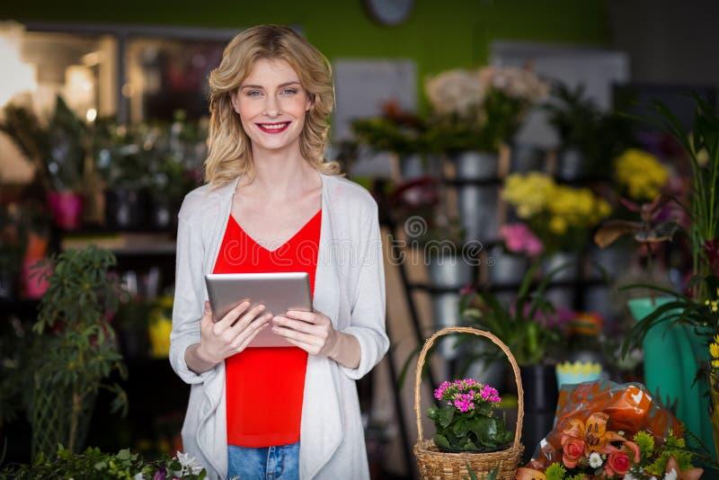 拿着在花店的愉快的女性卖花人数字式片剂 免版税库存图片