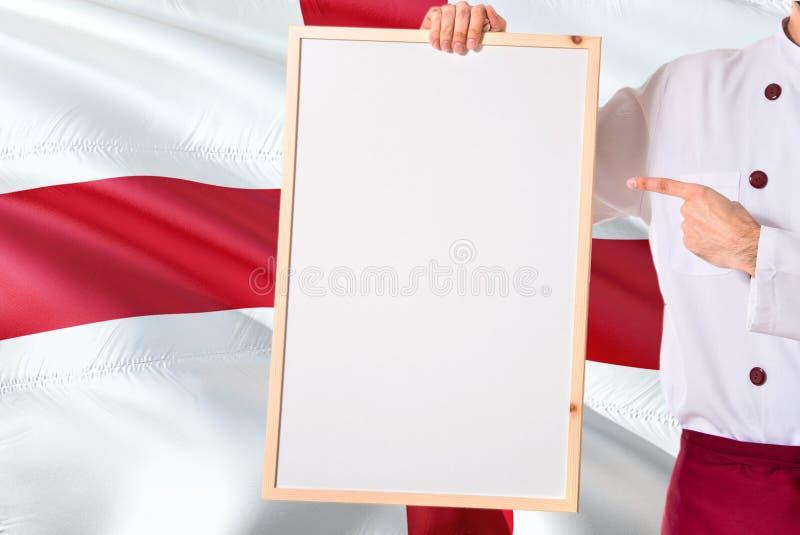 拿着在英国旗子背景的英国厨师空白的whiteboard菜单 烹调指向文本的佩带的制服空间 免版税库存图片