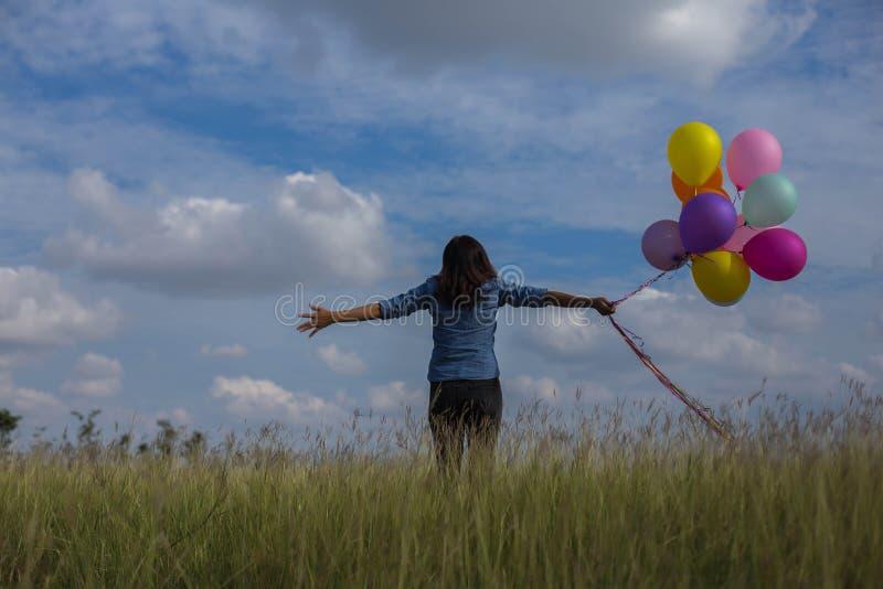 拿着在草地的美女一个透明球 免版税库存图片