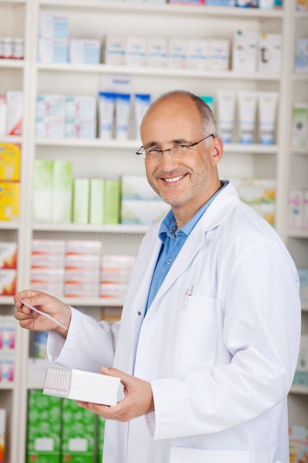 拿着在药房的药剂师医学和处方纸 免版税库存图片