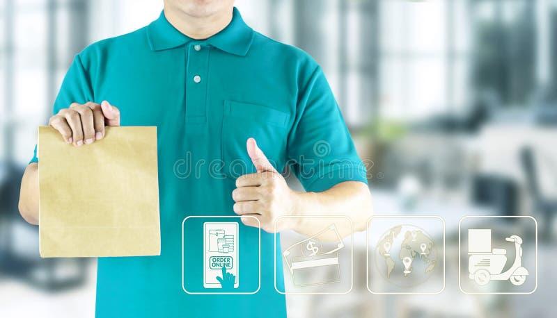 拿着在蓝色制服和象媒介的送货人手纸袋提供的包裹顺序网上便当送货服务 图库摄影