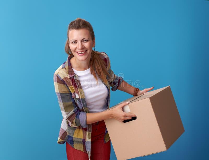 拿着在蓝色的微笑的活跃妇女纸板箱 库存照片