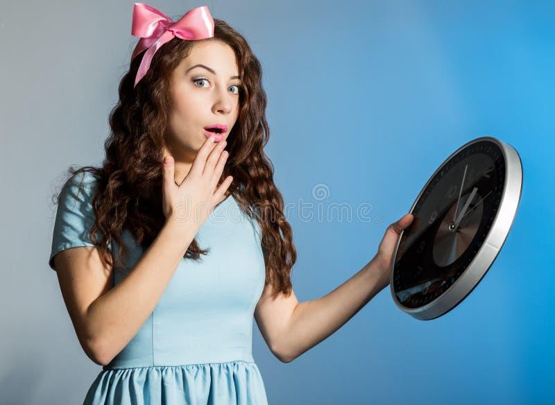拿着在蓝色背景的一件蓝色礼服的美丽的画报女孩大时钟 免版税库存照片