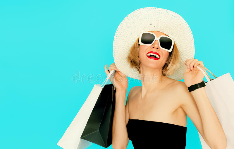 拿着在蓝色背景的愉快的购物妇女袋子 免版税库存图片
