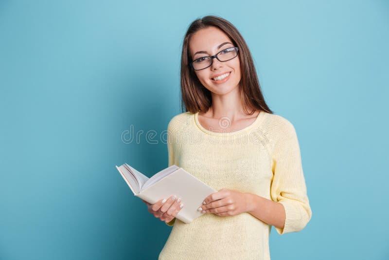 戴拿着在蓝色背景的眼镜的年轻俏丽的女孩书 免版税图库摄影