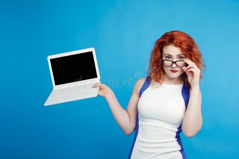 拿着在蓝色背景的美丽的红发女孩膝上型计算机孤立 安置文本 免版税库存照片