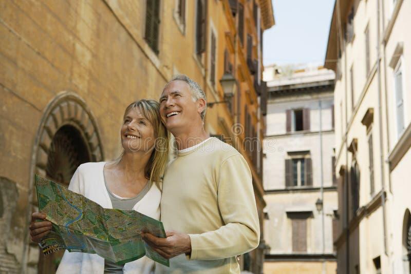 拿着在街道上的夫妇地图在罗马 库存照片