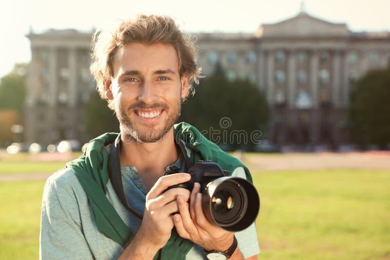 拿着在街道上的年轻男性摄影师专业照相机 图库摄影