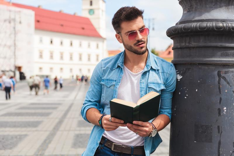 拿着在街道上的轻松的人一本书看支持 库存图片