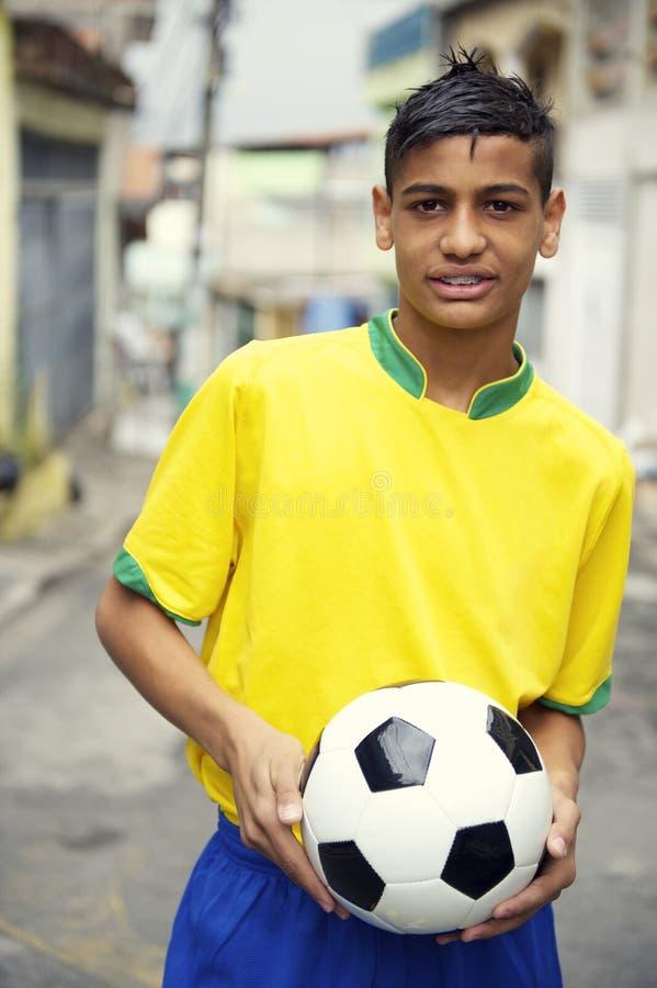 拿着在街道上的年轻巴西足球运动员足球 免版税图库摄影