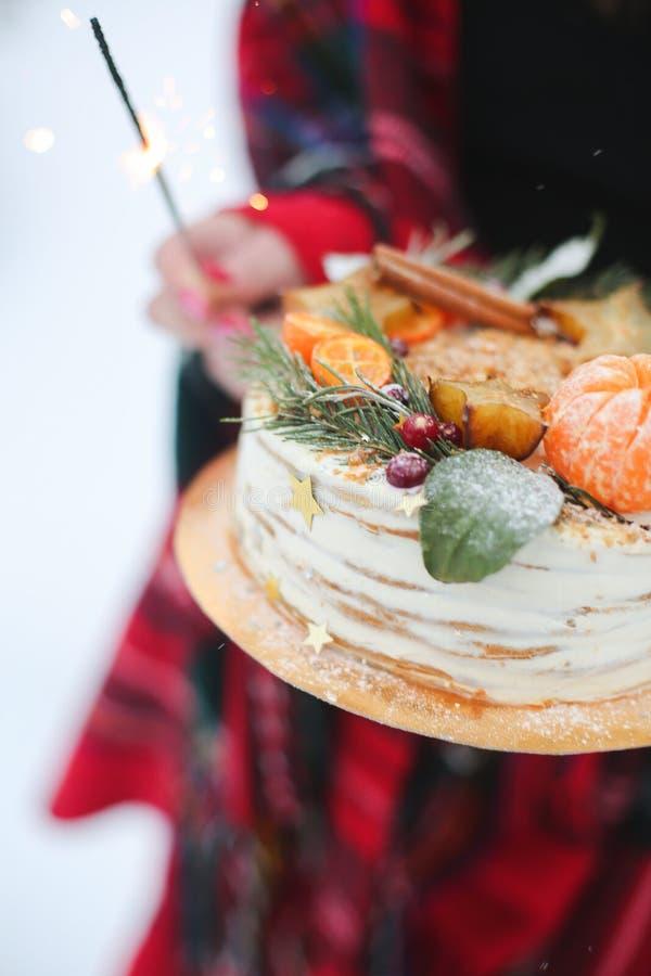 拿着在街道的年轻女人圣诞节蛋糕 下雪,闪烁发光物 库存照片