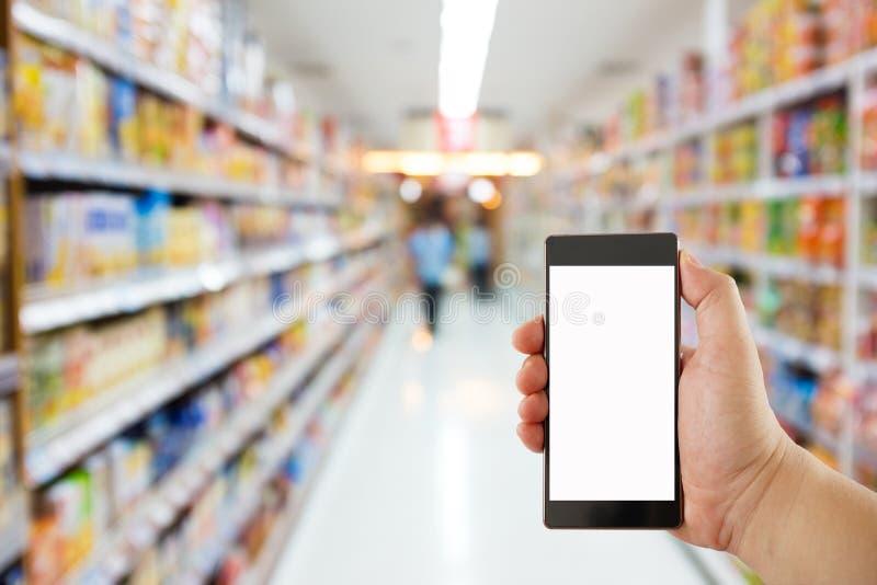 拿着在超级市场迷离背景的手手机 库存照片