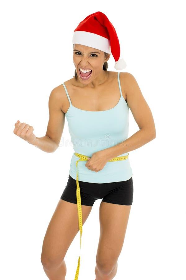 拿着在身体腰部的健身衣裳和圣诞老人圣诞节帽子的妇女措施磁带 免版税库存照片