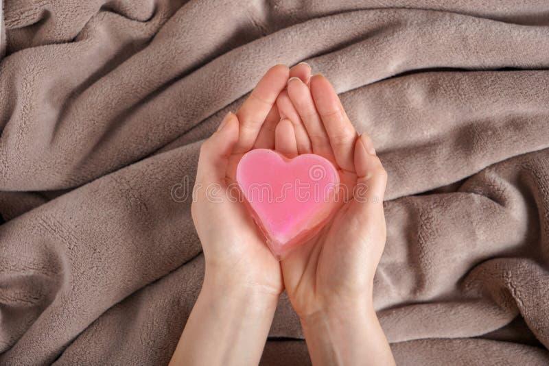 拿着在软的格子花呢披肩的妇女装饰心脏,顶视图 库存图片