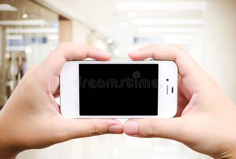 拿着在迷离商店背景的手巧妙的电话 免版税库存照片