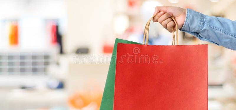 拿着在迷离商店背景,横幅w的手红色购物袋 免版税库存图片
