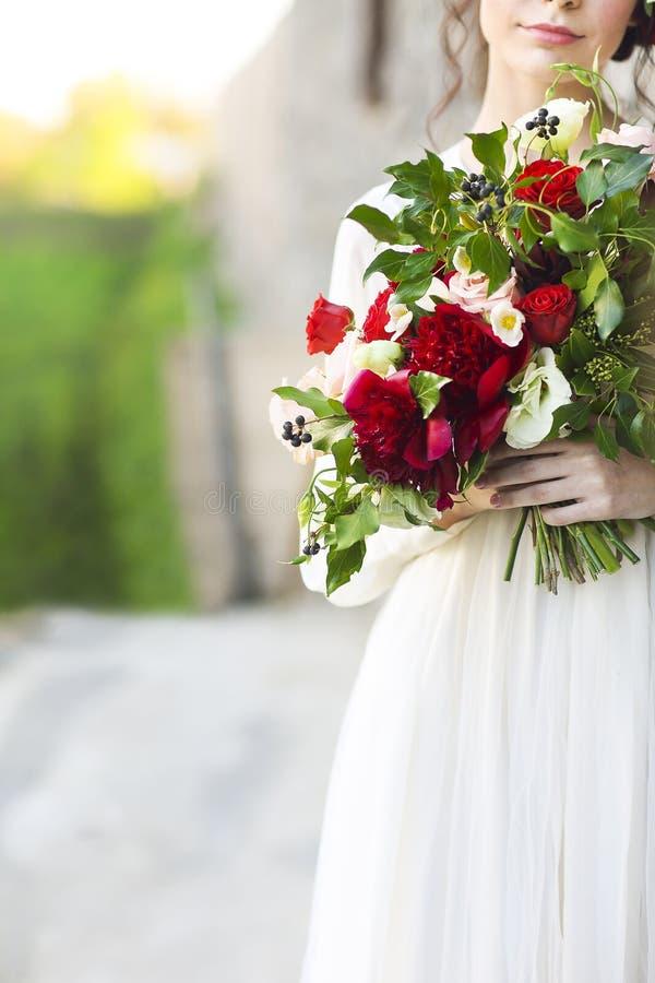 拿着在迷离的白色婚礼礼服的新娘美丽的花束 免版税库存图片