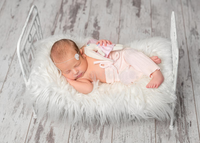 拿着在逗人喜爱的小的床上的新出生的睡觉的婴孩玩具 库存图片