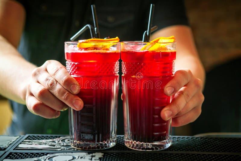 拿着在酒吧柜台的侍酒者两个鸡尾酒 免版税库存照片