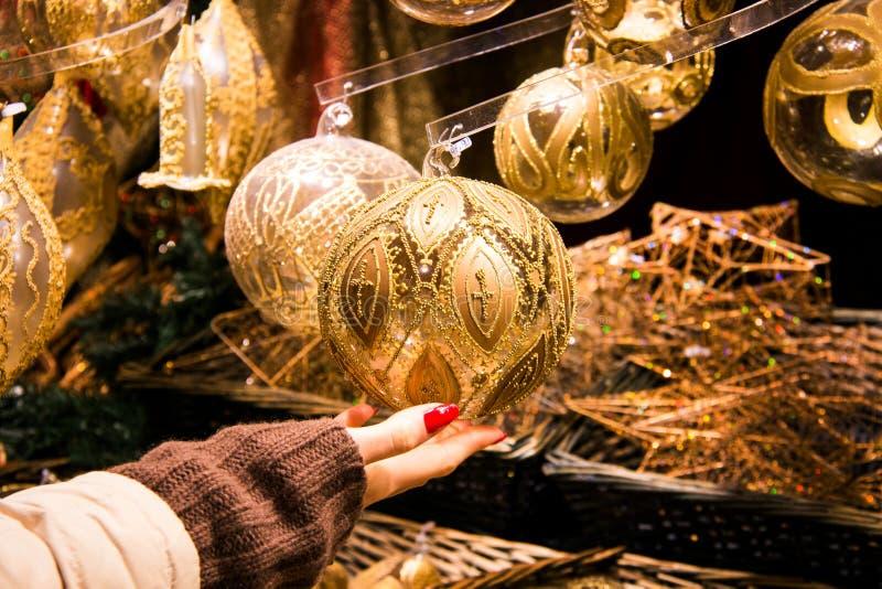 拿着在金子颜色的妇女手美妙地被制作的圣诞装饰球与装饰设计 免版税库存图片