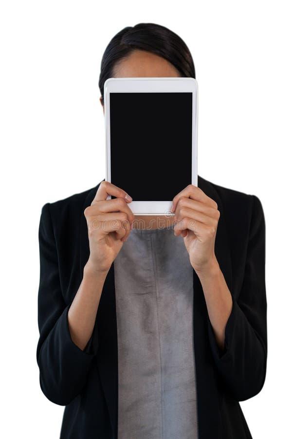 拿着在面孔前面的女实业家片剂计算机 库存照片