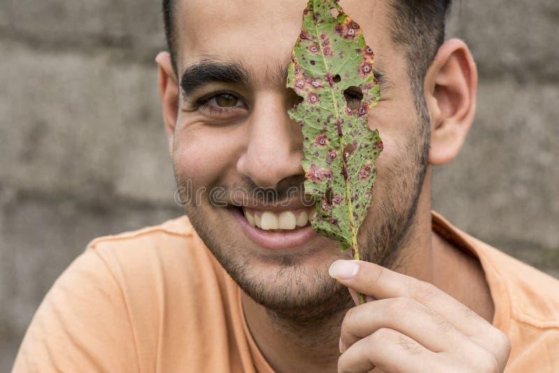 拿着在面孔前面的愉快的年轻人废墟叶子在室外 免版税图库摄影